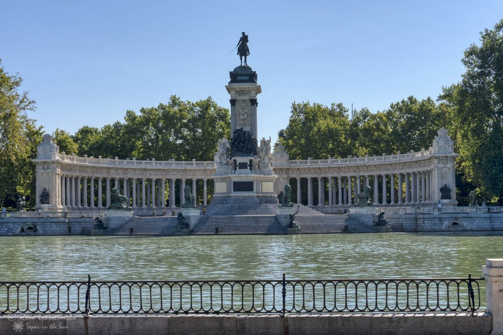 El Retiro, Madrid. The lake with the King Alfonso XII monument and the semi-circular colonnade behind.