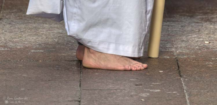 A nazareno walking barefoot in a Semana Santa procession