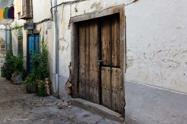 An old wooden door with cheap and weak padlock.