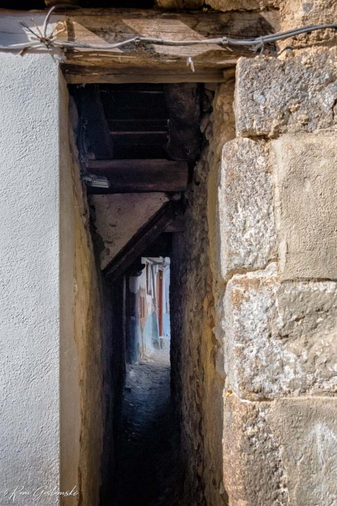 A very narrow passage between houses.
