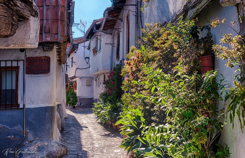 A pretty, narrow cobbled street in Hervás with potted plants